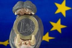 Una euro moneta in bocca della figurina dell'ippopotamo Fotografia Stock