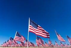 Una exhibición de banderas americanas con un fondo del cielo Imagen de archivo libre de regalías
