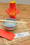 Una exhibición hecha en casa de la linterna con un par de palillos, de un cuenco y de un sobre rojo con una Feliz Año Nuevo de la Fotos de archivo libres de regalías