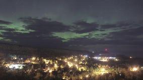 Una exposición larga de la noche granangular del verde Aurora Borealis sobre una pequeña orilla del norte, ciudad 4K UHD Timela almacen de video