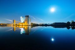 Una fábrica teniendo en cuenta una Luna Llena Fotografía de archivo libre de regalías