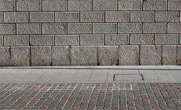 Una fachada de piedra de los bloques, una acera de piedra natural gris de las losas y un porphyr imagen de archivo