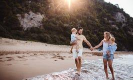 Una famiglia con due bambini del bambino che camminano sulla spiaggia sulla vacanza estiva al tramonto fotografia stock