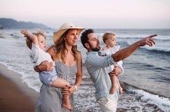 Una famiglia con due bambini del bambino che camminano sulla spiaggia sulla vacanza estiva al tramonto fotografie stock