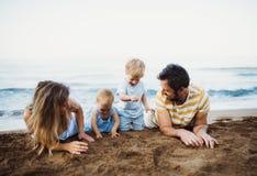 Una famiglia con due bambini del bambino che si trovano sulla spiaggia di sabbia sulla vacanza estiva fotografie stock libere da diritti