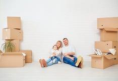 Una famiglia con le scatole si muove verso una nuova casa contro una parete bianca immagini stock libere da diritti