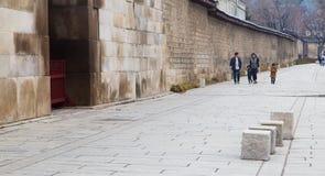 Una famiglia coreana che cammina accanto alle pareti del palazzo di Gyeongbokgung immagine stock