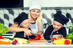 Una famiglia dei cuochi Cibo sano La madre ed i bambini prepara l'insalata di verdure in cucina fotografia stock libera da diritti