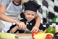 Una famiglia dei cuochi Cibo sano La madre ed i bambini prepara l'insalata di verdure in cucina fotografie stock libere da diritti