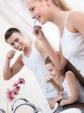 Una famiglia della spazzola tre i loro denti Fotografie Stock