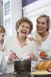 Una famiglia delle tre generazioni in cucina che cucina pranzo Fotografia Stock Libera da Diritti