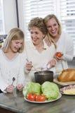 Una famiglia delle tre generazioni in cucina che cucina pranzo Fotografia Stock