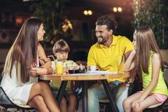 Una famiglia di quattro membri che ha grande tempo in un ristorante Fotografia Stock