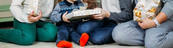 Una famiglia di quattro si siede sul pavimento vicino all'albero e scambia i regali spieghi i regali immagini stock