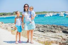 Una famiglia di tre che cammina lungo la spiaggia tropicale Fotografie Stock Libere da Diritti