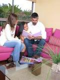 Una famiglia di tre che legge. Fotografia Stock