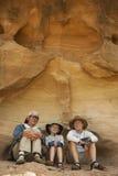 Una famiglia di tre che si siedono nel riparo della roccia Fotografia Stock