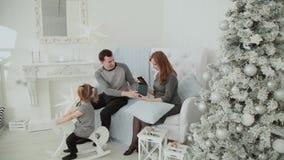 Una famiglia di tre che si siedono sullo strato e che parlano sulla notte di San Silvestro, Natale 2019 archivi video