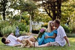 Una famiglia di tre davanti al giardino floreale immagine stock