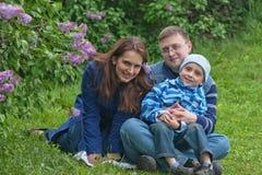 Una famiglia di tre felice ha un resto in giardino lilla Fotografie Stock