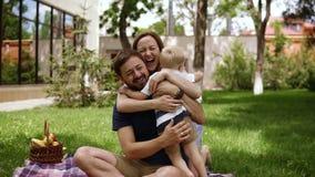 Una famiglia di tre felice I genitori in casuale stanno sedendo su un plaid con le mani aperte e stanno sorridendo al loro piccol video d archivio