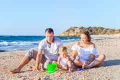 Una famiglia di tre felice - madre, padre e figlia incinti divertendosi, giocando con la sabbia e le coperture sulla spiaggia Vac Immagine Stock Libera da Diritti