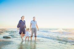 Una famiglia di tre felice - madre, padre e figlia incinti, tenendosi per mano, laughhing e divertendosi camminata sulla spiaggia Immagini Stock Libere da Diritti