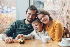 Una famiglia di tre felice madre, padre e figlio, sedentesi nel ristorante Fotografia Stock Libera da Diritti