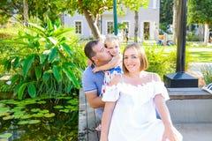 Una famiglia di tre felice - moglie, padre e figlia incinti divertendosi vicino allo stagno con le ninfee nel parco Ricreazione d Immagine Stock