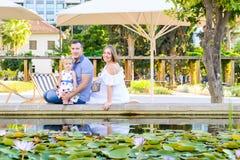 Una famiglia di tre felice - moglie, padre e figlia incinti divertendosi vicino allo stagno con le ninfee nel parco Ricreazione d Fotografie Stock