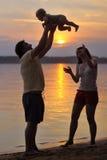 Una famiglia di tre felice sulla spiaggia Immagini Stock Libere da Diritti