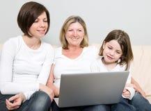 Una famiglia di tre generazioni per mezzo di un computer portatile Fotografie Stock Libere da Diritti