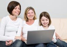 Una famiglia di tre generazioni per mezzo di un computer portatile Fotografia Stock Libera da Diritti