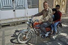 Una famiglia di tre iraniani sta guidando la motocicletta sulla via della città Immagine Stock