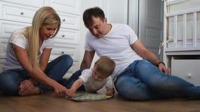 Una famiglia di tre in magliette bianche e blue jeans che si siedono sul pavimento della loro camera da letto che gioca con il ra stock footage
