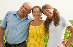Una famiglia di tre sopra un campo Immagini Stock