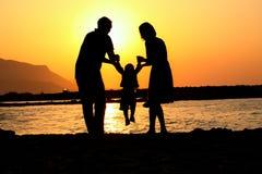 Una famiglia felice della siluetta di gioco tre Immagini Stock Libere da Diritti