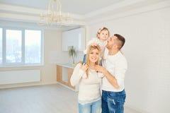 Una famiglia felice gioca insieme con un bambino in un tè luminoso della casa immagine stock libera da diritti