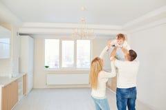 Una famiglia felice gioca insieme con un bambino in un tè luminoso della casa immagini stock libere da diritti