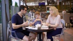 Una famiglia felice pranza ad un ristorante, un marito e una moglie hanno ordinato una pizza, il loro piccolo figlio è soddisfatt stock footage
