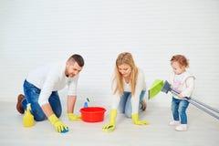 Una famiglia felice sta lavando il pavimento fotografie stock