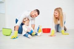 Una famiglia felice sta lavando il pavimento immagini stock libere da diritti