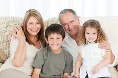 Una famiglia felice sul loro sofà che esamina la macchina fotografica Fotografia Stock