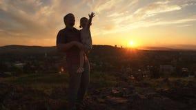 Una famiglia felice sul tramonto, il padre sta tenendo sua figlia lei armi archivi video