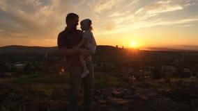 Una famiglia felice sul tramonto, il padre sta tenendo sua figlia lei armi video d archivio