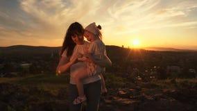Una famiglia felice sul tramonto, madre sta tenendo sua figlia lei armi stock footage