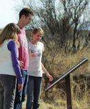 Una famiglia legge un segno a Murray Springs Clovis Site immagini stock libere da diritti