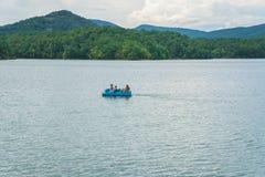 Una famiglia su un crogiolo di pagaia blu alla baia di Carvins situata nella contea di Botetourt, la Virginia, U.S.A. fotografia stock