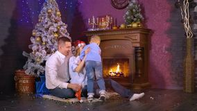 Una familia alegre de tres personas debajo del árbol de navidad Concepto de familia feliz HD almacen de metraje de vídeo