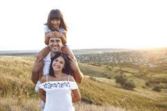 Una familia alegre está sonriendo en la puesta del sol foto de archivo libre de regalías